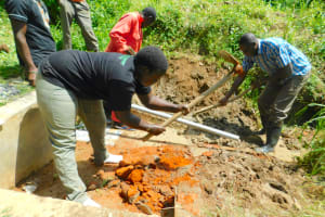 The Water Project: Ikonyero Community, Jesse Spring -  Team Leaders And Artisan Break Down Stairs And Walls