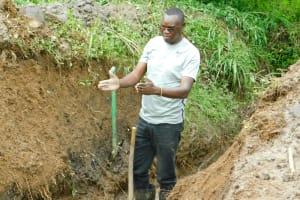 The Water Project: Ikonyero Community, Jesse Spring -  Regional Director Humphrey Buradi Supervising Work