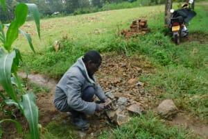 The Water Project: Eshiakhulo Community, Asman Sumba Spring -  Community Member Breaking Rocks Into Gravel