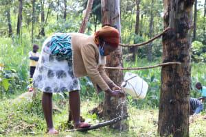 The Water Project: Bukhaywa Community, Ashikhanga Spring -  Wahing Her Hands At The Spring Handwashing Station