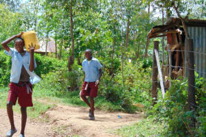 The Water Project: Jivuye Primary School -  Pupils Carrying Water From Home