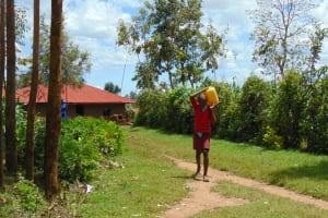 The Water Project: Jivuye Primary School -  Pupil Carrying Water From Home