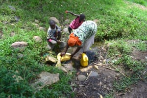The Water Project: Shianda Township Community, Olingo Spring -  Collecting Water From Olindo Spring