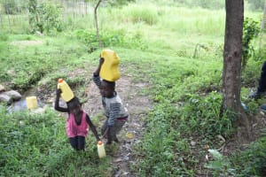 The Water Project: Shianda Township Community, Olingo Spring -  Taking Water Home From Olingo Spring