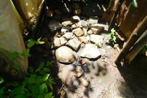 The Water Project: Eshimuli Community, Mbayi Spring -  Bathing Shelter Rock Floor