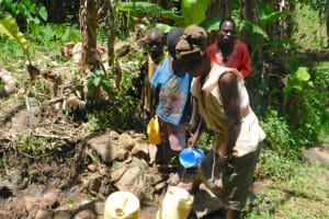 The Water Project: Eshimuli Community, Mbayi Spring -  Collecting Water From Mbayi Spring