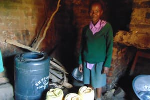The Water Project: KG Jeptorol Primary School -  Pupil Next To Home Water Storage