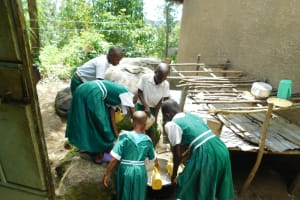 The Water Project: Kitambazi Primary School -  Students Pour Water Into A Pot For Later Use