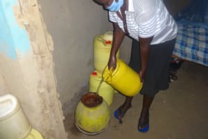 The Water Project: Mahira Community, Mukalama Spring -  Pouring Water Into Traditional Clay Pot For Storage