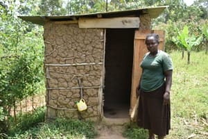 The Water Project: Shamoni Community, Shiundu Spring -  Beryl Outside Her Latrine With Handwashing Station