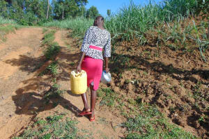 The Water Project: Indulusia Community, Osanya Spring -  Lillian Carrying Water Home