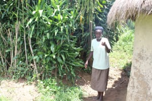 The Water Project: Mayuge Community, Ucheka Spring -  Showing Us Her Bathing Room Behind Her In Trees