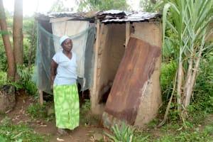 The Water Project: Shibikhwa Community, Musotsi Spring -  Madam Irene Outside Her Bathing Shelter And Latrines