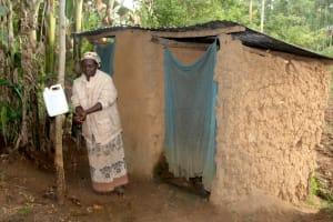 The Water Project: Shibikhwa Community, Musotsi Spring -  Miriam Handwashing Outside Her Latrine