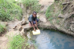 The Water Project: Mukhuyu Community, Gideon Kakai Chelagat Spring -  Balancing To Fetch Water