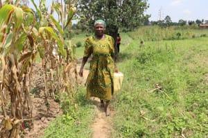 The Water Project: Mukhuyu Community, Gideon Kakai Chelagat Spring -  Madam Kakai Carrying Water