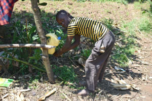 The Water Project: Makunga Community, Tabarachi Spring -  Elvis Washing His Hands Using A Leaky Tin