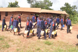 The Water Project: Ithingili Primary School -  Students Carrying Water