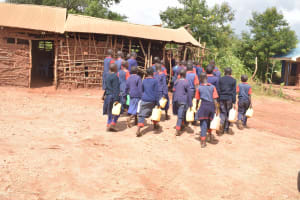 The Water Project: Ithingili Primary School -  Students Walking With Water Containers