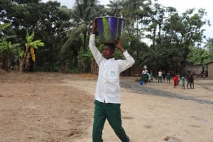 The Water Project: Lokomasama, Matong, DEC Primary School -  Student Carrying Water