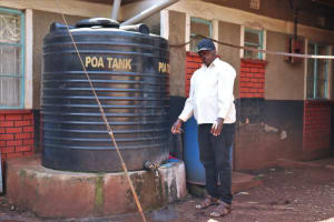 The Water Project: Irumbi Community, Okang'a Spring -  Pius Airdrying His Hands Next To His Rain Tank