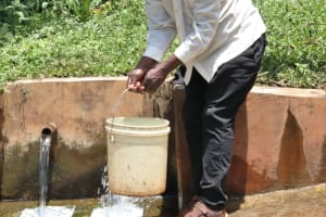 The Water Project: Irumbi Community, Okang'a Spring -  Pius Taking Water From The Spring