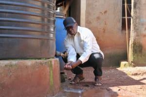 The Water Project: Irumbi Community, Okang'a Spring -  Pius Washing His Hands At His Home Rain Tank