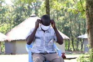 The Water Project: Bung'onye Community, Shilangu Spring -  Wilson Puting His Mask On