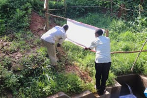 The Water Project: Mahira Community, Wora Spring -  Installing Covid Prevention Reminders Chart