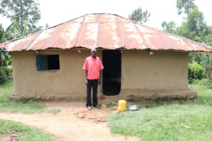The Water Project: Handidi Community, Kadasia Spring -  Zachariah In Front Of His House