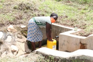 The Water Project: Ematetie Community, Weku Spring -  At Weku Spring Fetching Water
