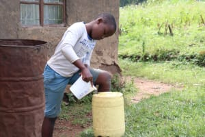 The Water Project: Ematetie Community, Chibusia Spring -  Joshua Refilling The Handwashing Container