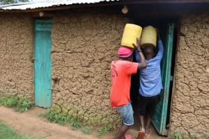 The Water Project: Shamoni Community, Laban Ang'ata Spring -  Carrying Water Into Their House