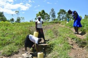 The Water Project: Shianda Community, Akhonya Spring -  People Drawing Water