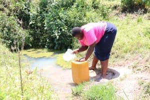The Water Project: Elwichi Community, Mulunda Spring -  Dora Carefully Fetching Water