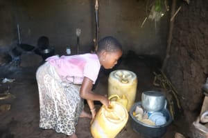 The Water Project: Lukala West Community, Luka Spring -  Setting Down Her Jerrican Inside The Kitchen