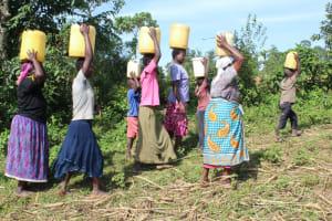 The Water Project: Litinye Community, Vuyanzi Spring -  Carrying Water