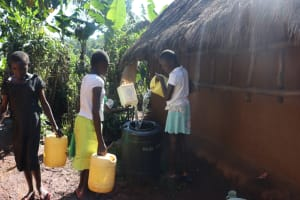 The Water Project: Lukala West Community, Angatia Spring -  Pouring Water Into Central Storage Bin