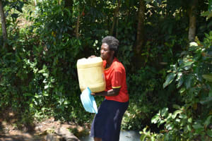 The Water Project: Shikokhwe Community, Mulika Spring -  Mounting Water On Her Head To Carry