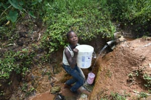 The Water Project: Malekha West Community, Soita Spring -  Mounting Her Bucket On Her Head