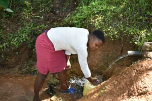 The Water Project: Malekha West Community, Soita Spring -  Rinsing Her Container