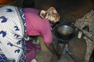 The Water Project: Shianda Community, Govet Lumbasi Spring -  Adding Firewood To The Stove