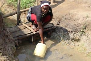 The Water Project: Makhwabuyu Community, Shirandula Spring -  Njeri Collecting Water