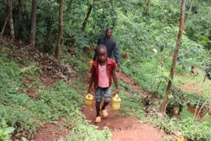 The Water Project: Shamakhokho Community, Wizula Spring -  Andrew Carrying Water