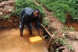 The Water Project: Shamakhokho Community, Wizula Spring -  Syllas Shigali Fetching Water