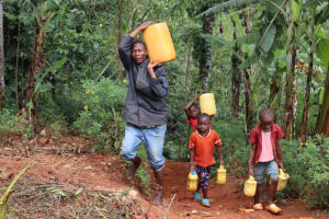 The Water Project: Shamakhokho Community, Wizula Spring -  Syllas Carrying Water
