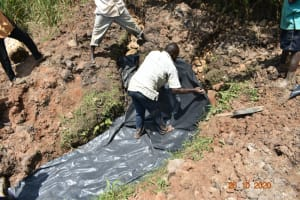 The Water Project: Mahola Community, Oyula Spring -  Laying Plastic Tarp