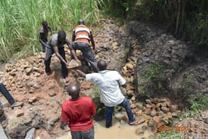 The Water Project: Mahola Community, Oyula Spring -  Backfilling With Large Rocks