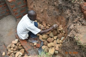The Water Project: Mahola Community, Oyula Spring -  Building Up Stone Pitching