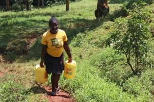The Water Project: Shikoye Community, Kwa Witinga Spring -  Spring User Carrying Water